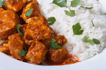 Rice and chunks of chicken curry on a plate